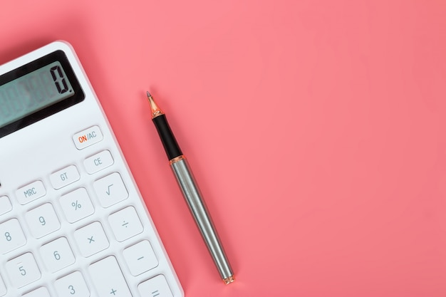 White calculator and pen on a bright pink background, marketing and financial concepts