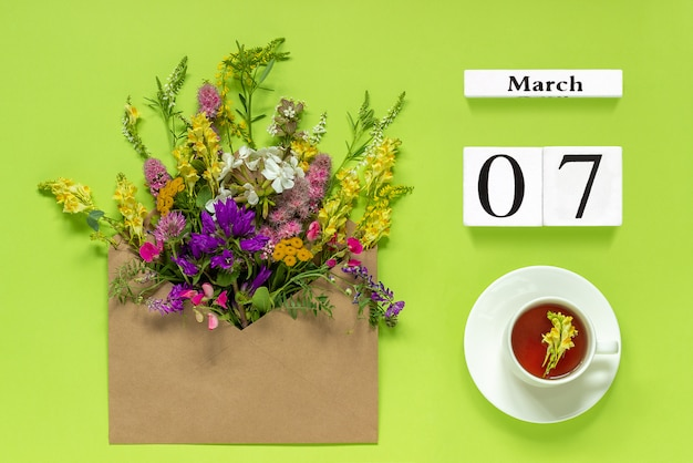 White calendar march 7. cup of tea, kraft envelope with multi colored flowers on green