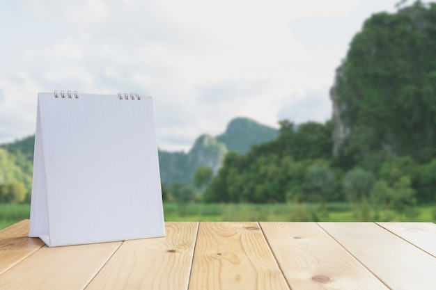 White calendar on wood table on nature background and copy space mock up.