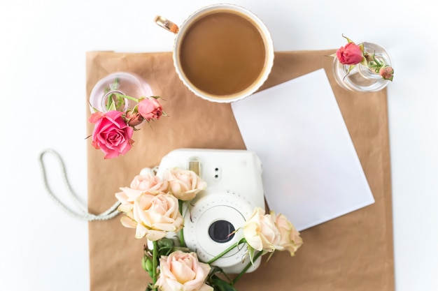 White camera on the desktop among the flowers next to a cup of coffee
