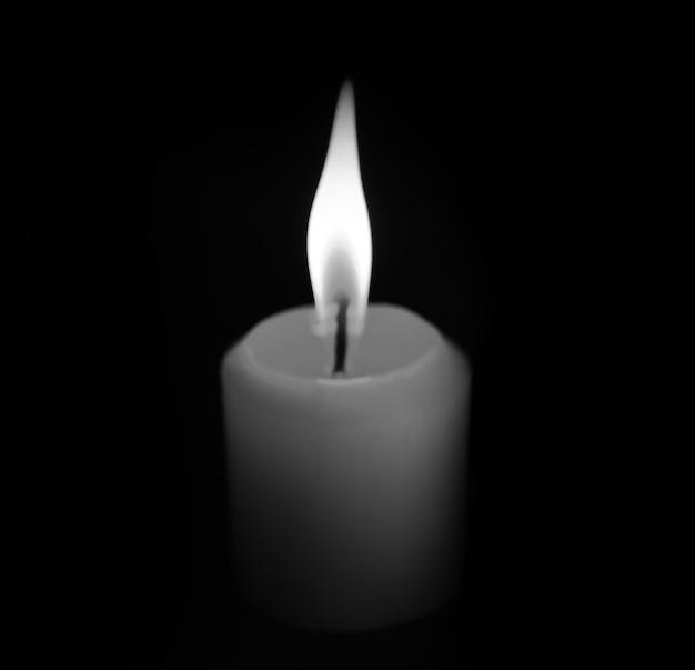 White candle on black background