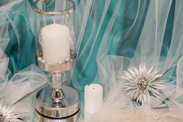 White candle in the glass candlestick with decorative aquamarine silk