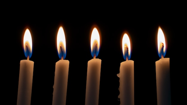 White candles burning in the dark with lights glow