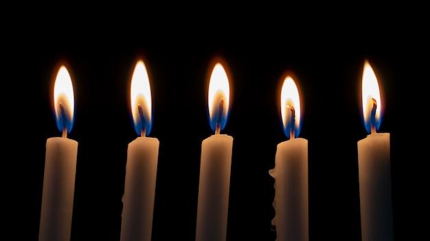 불빛이 빛나는 어둠 속에서 불타는 하얀 양초