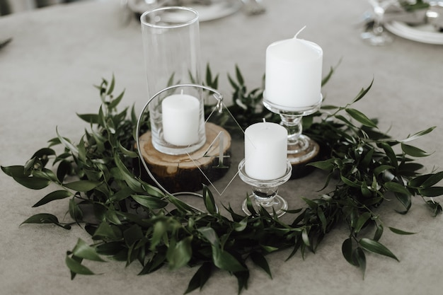White candles on the glass candlestick on the grey background surrounded with green leaves