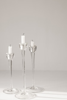 White candles in glass candlesticks on a white background interior design or decor
