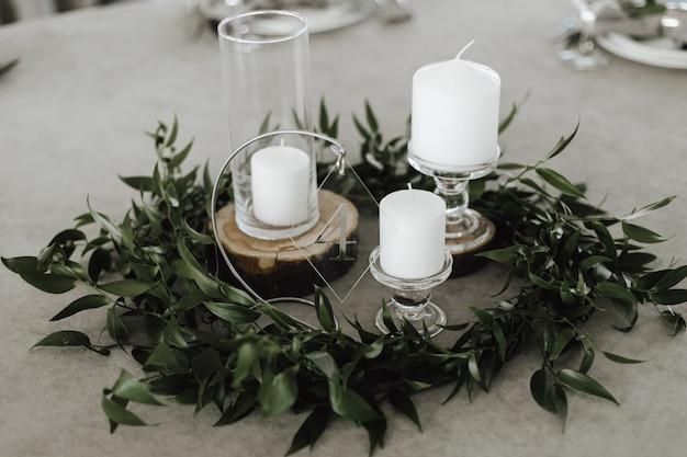Белые свечи на стеклянном подсвечнике на сером фоне в окружении зеленых листьев