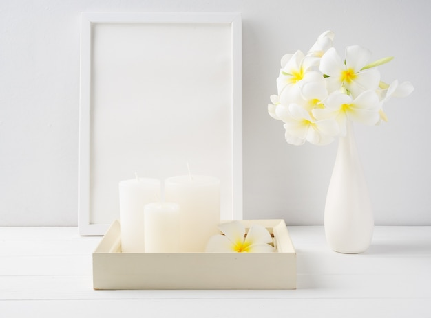흰색 나무 쟁반에 흰색 촛불, 흰색 나무 테이블 룸 인테리어, 스파 부드러운 톤 정물화에 현대 세라믹 꽃병에 포스터 프레임과 plumeria 꽃을 모의