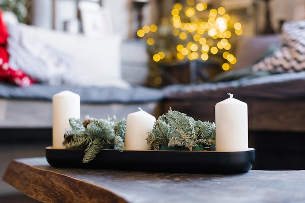 White candles and pine branches in christmas home decor
