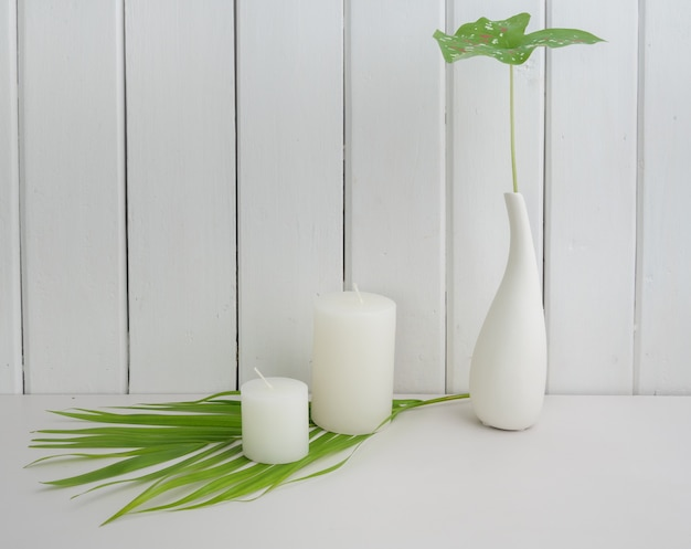 White candles set on fresh green coconut palm leaf on wooden table and wall background,clean white concept