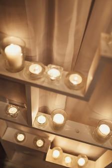 Candele bianche brillano sugli scaffali