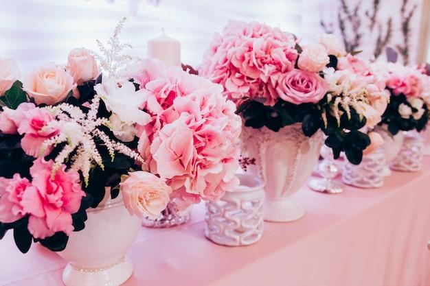 テーブルの上の豪華なブーケピンクのバラとアジサイの周りに白いキャンドルが立ちます。