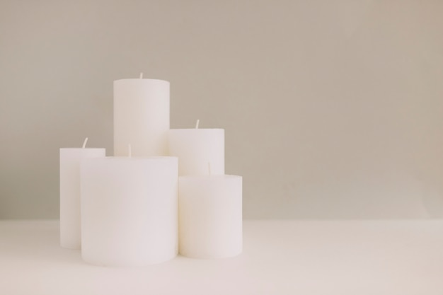 White candles on tabletop against colored backdrop