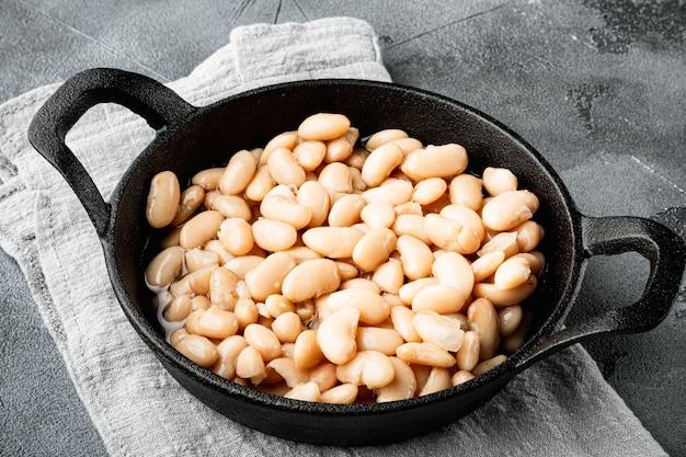 회색 돌 배경에 주철 프라이팬에 흰색 통조림 콩 세트