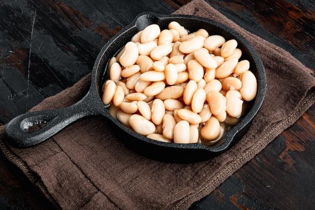 흰색 통조림 콩 세트, 주철 프라이팬, 오래된 어두운 나무 테이블 배경