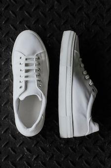White canvas sneakers on metal floor