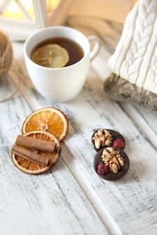 Белая шапка чая с лимоном. смешайте орехи, сухофрукты и шоколад на белом фоне