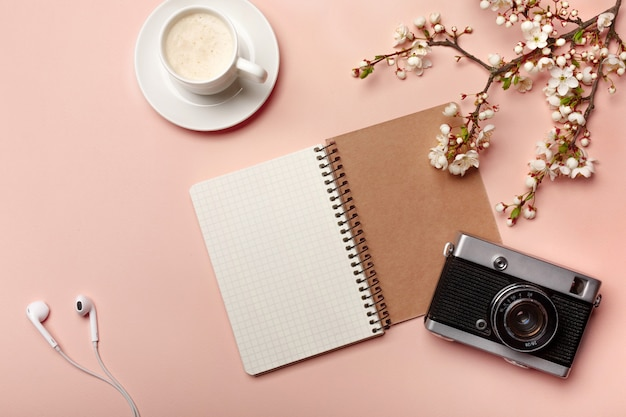A white cappuccino cup with sakura flowers, a notebook, a camera, headphones