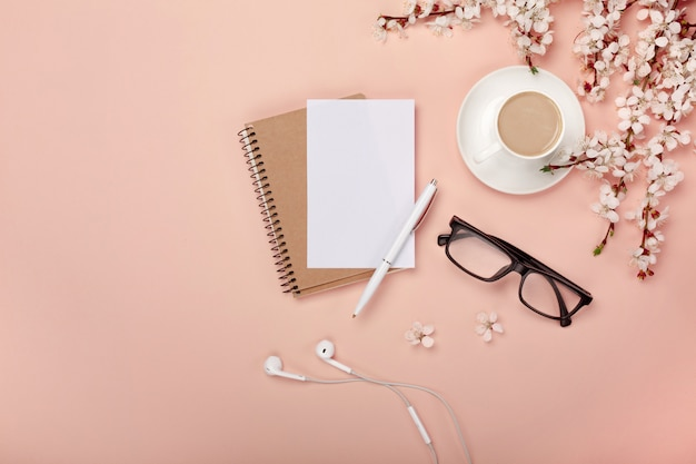 A white cappuccino cup with sakura flowers, notebook, headphones, pen and glasses