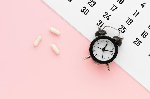 분홍색 배경에 흰색 캡슐, 달력 및 알람 시계. 의료 암살 일정. 건강 개념. 복사 공간이있는 평면 위치, 평면도.