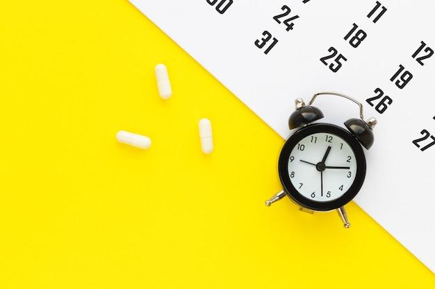 노란색 배경에 흰색 캡슐, 달력 및 알람 시계. 의료 암살 일정. 건강 개념. 복사 공간이있는 평면 위치, 평면도.