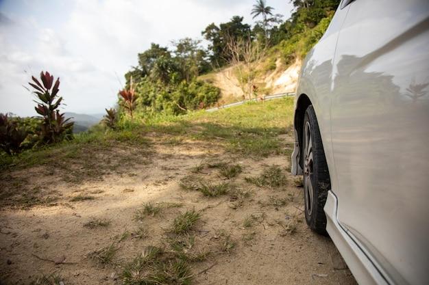 열대 지방의 절벽 측면에 있는 흰색 자동차와 바퀴가 닫힙니다.