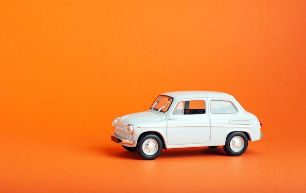 White car on colored background. model white retro toy car on orange background. miniature car with copyspace.