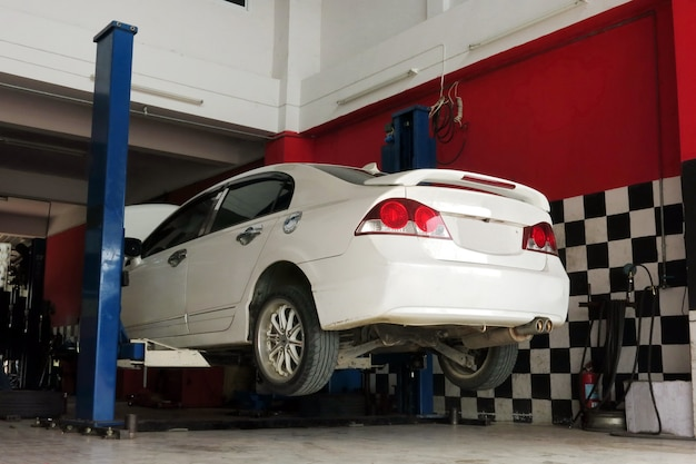 A white car is lifted up for the repairing process