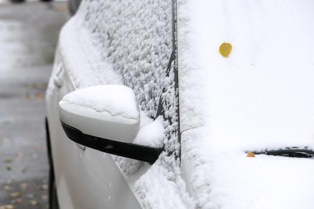 Белая машина припаркована возле жилого дома в городе, покрытого первым осенним снегом, фрагмент крупным планом