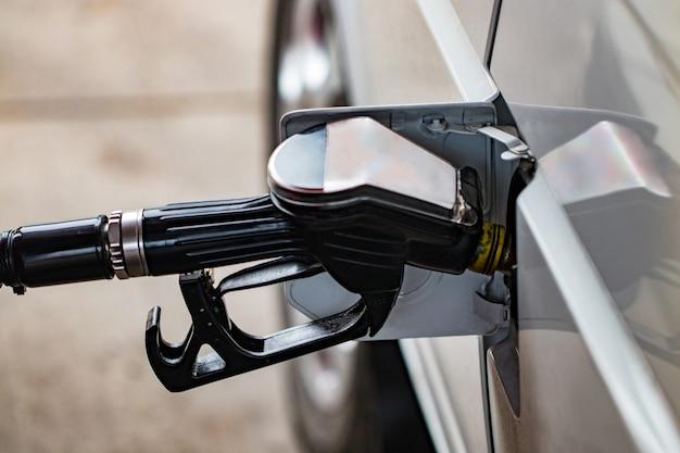 흰색 자동차는 가솔린 탱크 자동차의 필러 넥에있는 주유소 인 주유소로 급유됩니다.