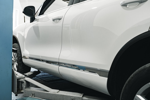 White car lifted in automobile service station close up