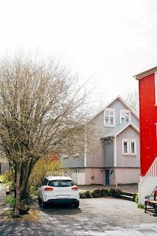 아이슬란드의 수도 레이캬비크 거리에 흰색 차가 집 밖에 주차되었습니다.