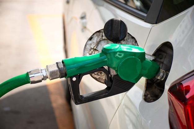 녹색 연료 노즐로 주유소에서 흰색 자동차 급유.