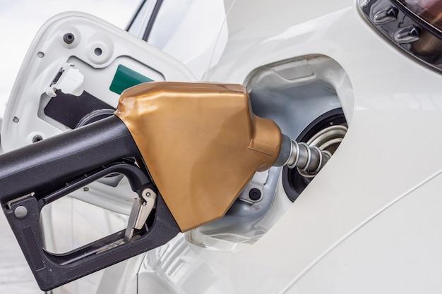 ガソリンスタンドで給油する白い車