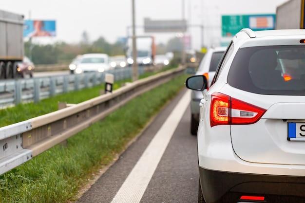 ラッシュアワーの高速道路の渋滞で待っている白い車