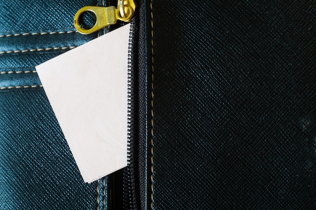 White card emerges from the zipper pocket on jeans