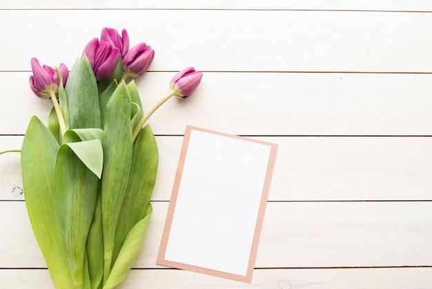 白い木製の背景の上に春のチューリップの上面図と白いカードまたはメニューカード。デザインをモックアップします。