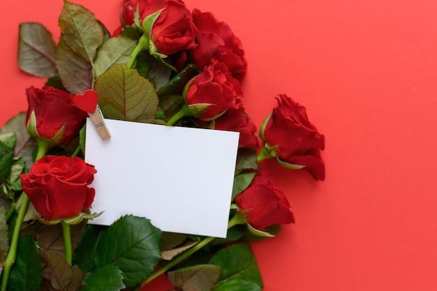 赤いバラを背景にテキストの場所が付いた白いカード、はがきバレンタインデー