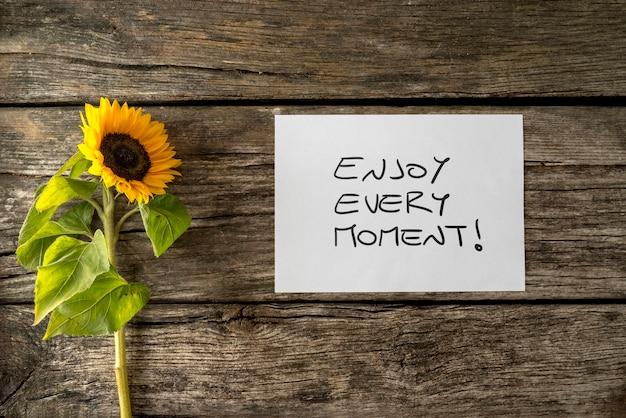 質感のある木製の机の上に咲く美しいひまわりの横にある「一瞬一瞬を楽しむ」メッセージが書かれた白いカードは、その瞬間をとらえ、充実した生活を送ることを奨励します。