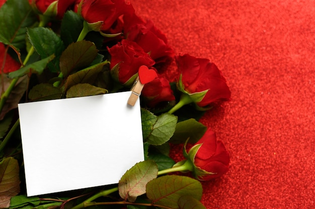 White card with a place for text against the background of red roses