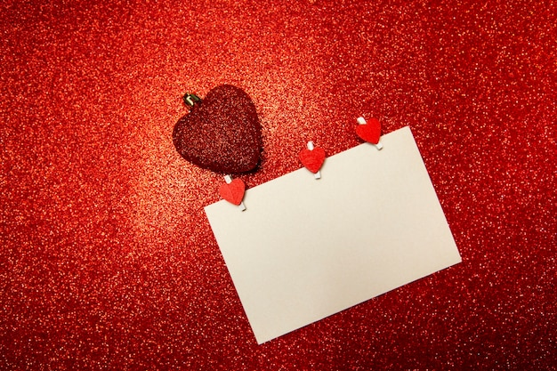 White card with red hearts-clothespins on red
