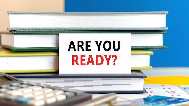 Белая карточка с текстом, вы готовы, стоит на столе на фоне сложенных книг, калькулятора, ручки, кредитной карты. бизнес и финансовая концепция. синий фон. расфокусировать.