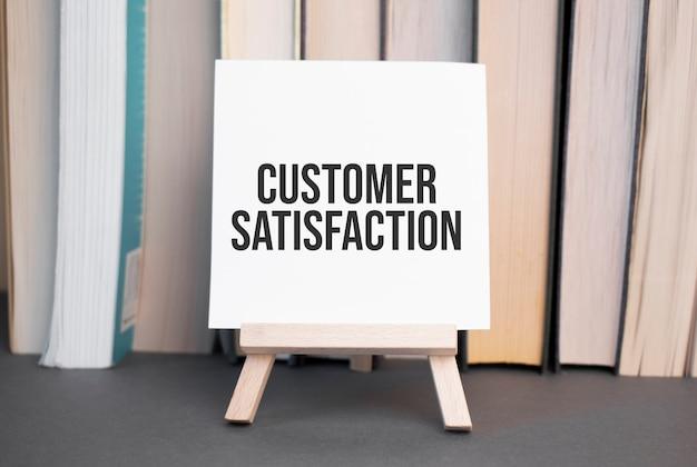 積み重ねられた本を背景に机の上に「顧客満足度」と書かれた白いカード
