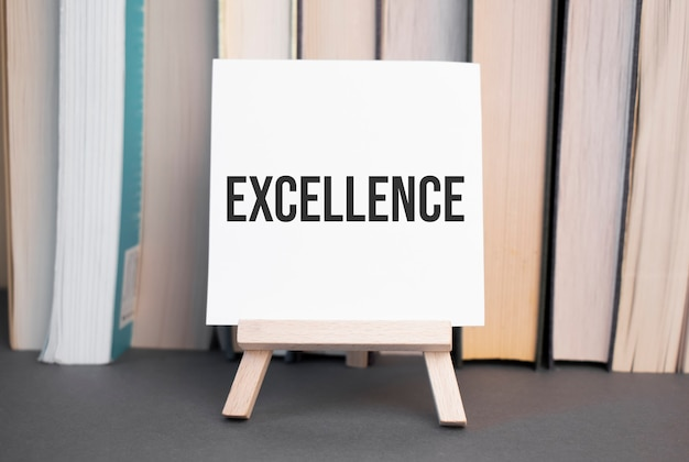 積み重ねられた本を背景に机の上に「エクセレンス」と書かれた白いカードが立っています。