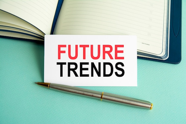 A white card with the text future trends on the background of an open paper notebook and a metal pen, gray background of the table