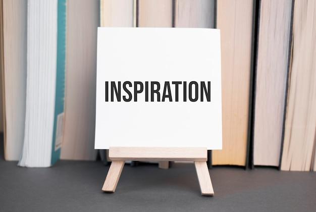 積み重ねられた本を背景に机の上にインスピレーションのテキストが書かれた白いカード