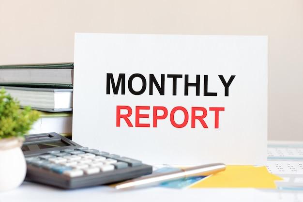 積み重ねられた本、電卓、ペン、緑の鉢植えの植物を背景に、テキストの月次レポートが付いた白いカードが机の上に立っています。ビジネスと財務の概念。セレクティブフォーカス。