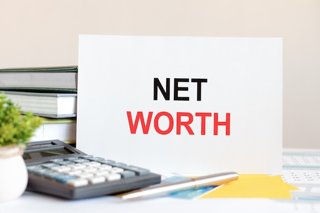 White card with text net worth stands on the desk against the background of books stacked, calculator, pen, green potted plant. business and financial concept. selective focus.