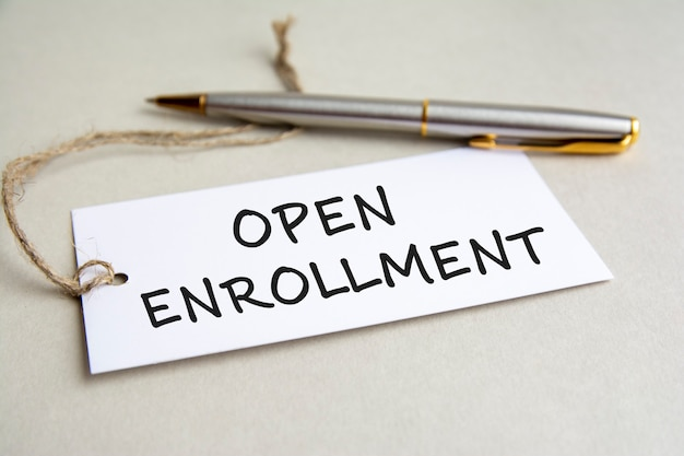 White card with text open enrollment with metal pen on gray background