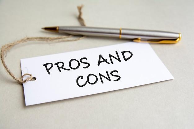 회색 배경에 금속 펜이 있는 텍스트 장단점이 있는 흰색 카드